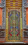 Decorative asian door with many colorful designs and patterns. Old ancient temple decorated wooden door with many colorful designs and patterns in Bali royalty free stock photography