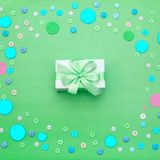 Decorative background with colored buttons in bulk and gift box. Top view flat lay. Square Royalty Free Stock Image