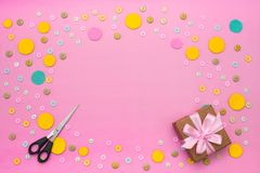 Decorative background with colored buttons in bulk and gift box. Top view flat lay stock photography