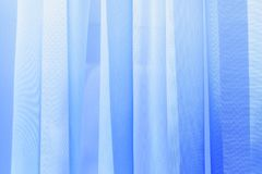 Undulate light of soft chiffon texture background. A decorative background of illuminated soft and gentle colored curtain made of lightweight tulle Stock Image