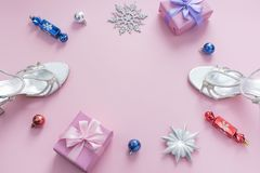 Decorative background pink Christmas composition Flat lay box gift ribbon bow snowflake sandals silver Christmas tree toys. Top view copy space stock photography