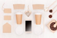 Decorative background for restaurant and coffee shop - two blank paper cups, phone, label, heart, coffee beans on white wood board. Top view stock image