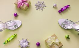 Decorative background yellow Christmas composition Flat lay box gift ribbon bow snowflake sandals silver Christmas tree toys. Top view copy space stock photo