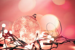 Decorative ball with garland lights for christmas holiday. At red background with abstract bokeh. Beautiful glass ball for christmas tree. Image like concept of royalty free stock image