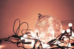 Decorative ball with with garland lights for christmas holiday. Decorative ball with garland lights for christmas holiday at red background. Beautiful glass ball royalty free stock image