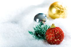 Decorative balls. Close-up of Christmas ball of red color decorated with golden stars in snow Stock Photography