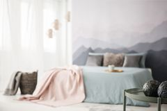 Decorative balls in cozy bedroom. Decorative balls on green table in cozy bedroom interior with pink blanket on bed Royalty Free Stock Photo