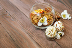 Decorative balls and dried orange in glass ball with cinnamon on a wooden table with a variety of beautiful items. Set for spa Stock Image