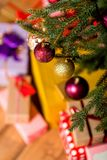 Decorative balls hanging on christmas tree. Over gift boxes Royalty Free Stock Image