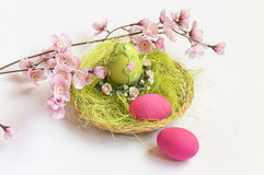 Decorative basket filled with flowers grass green eggs and pink eggs Stock Photography