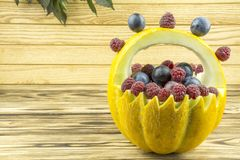Basket of melon filled with fruits, standing on a wooden background. Decorative basket yellow melon filled with fruit close-up royalty free stock photo