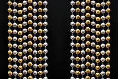 Decorative beads. Golden and silver decorative beads on a black background Stock Image