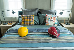 Decorative bed with pillow and football. Decorative bed with striped pillows and football at home Royalty Free Stock Photography