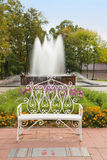 Decorative Bench in autumn park with fountain Stock Image