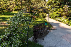 Decorative bench and a beautiful floral arch on the Avenue of the Park at the Sochi arboretum Royalty Free Stock Photos