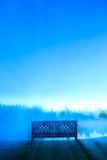 A decorative bench in front of a foggy pond, Stowe Vermont, USA Stock Image