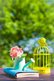 Decorative bird cage, book and flowers in can Royalty Free Stock Photography