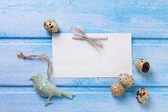 Decorative bird,  Easter eggs and empty tag on blue  wooden back Stock Image
