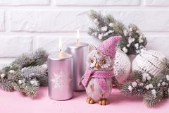 Decorative bird owl, silver candles, branches fur tree and balls. On pink background against white wall. Place for text royalty free stock images