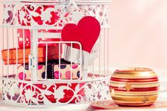 Decorative birdcage, presents, heart and candle. Stock Photos
