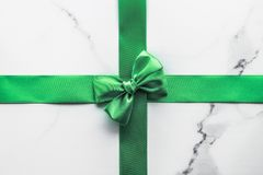 Green silk ribbon and bow on marble background, St Patricks day present or Christmas glamour gift decor for luxury digital brand,