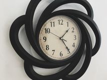 Decorative black clock on white wall. royalty free stock image