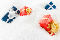Decorative blue and red gift box in the snow. Royalty Free Stock Image