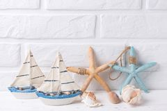 Free Decorative Boats, Shells And Sea Stars Near By White Brick Wal Royalty Free Stock Images - 114118549