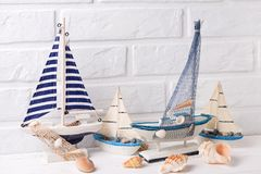 Decorative boats and  shells  near by white brick wall. Royalty Free Stock Photography