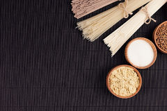 Decorative border of bundles raw noodles with ingredient in wooden bowls on black striped mat background with copy space, top view Stock Photography