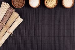 Decorative border of bundles raw noodles with ingredient in wooden bowls on black striped mat background with copy space, top view Royalty Free Stock Photos