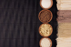 Decorative border of bundles raw noodles with ingredient in wooden bowls on black striped mat background with copy space, top view Stock Image