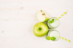 Decorative border of green apple fruit smoothie in glass jars with straw, mint leaves, cut apples, top view. Stock Photo