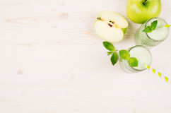 Decorative border of green apple fruit smoothie in glass jars with straw, mint leaves, cut apples, top view. Stock Images