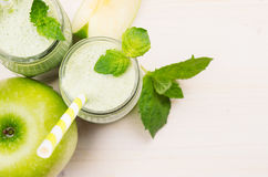 Decorative border of green apple fruit smoothie in glass jars with straw, mint leaves, cut apples, top view. White wooden board ba Royalty Free Stock Photos