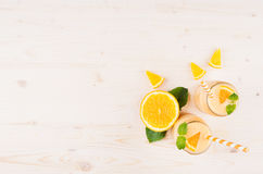 Decorative border of orange citrus smoothie in glass jars with straw, mint leaf, cut orange, top view. Stock Photos