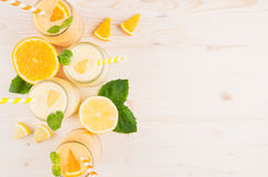Decorative border of orange and yellow lemon smoothie in glass jars with straw, mint leaf, top view. Stock Images