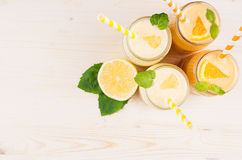 Decorative border of orange and yellow lemon smoothie in glass jars with straw, mint leaf, top view. Royalty Free Stock Photos
