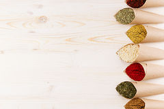 Decorative border of various powder spices close-up in paper corners on white wooden board with copy space. Stock Photography