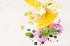 Decorative border of yellow and violet fruit smoothie in glass jars with straw, mint leaves, mango slices, berry, top view. Royalty Free Stock Photography