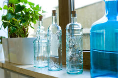 Decorative bottles from blue glass on a windowsill. With flowers royalty free stock photo
