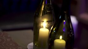 Decorative bottles with candles inside. Clip. Candles inside small bottle. Summer homemade decoration, glass jar and