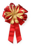 Decorative bow. Small golden bow over the big red bow stock photos