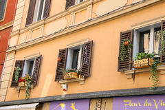 Decorative box with flowers over French food and wine shop. Bologna, Italy - August 18, 2014: Champagne box with flower pots on the windows used to advertise of Stock Photography