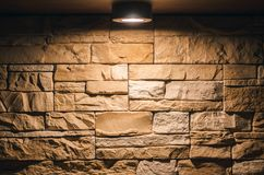 Decorative brick wall with lightbulb lamp above. Textured brick wall abstract background with copy space in the light of lamp Royalty Free Stock Photos