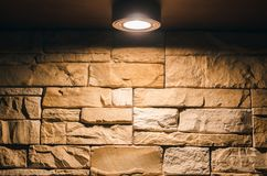 Decorative brick wall with lightbulb lamp above. Textured brick wall abstract background with copy space in the light of lamp Stock Photo