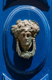 Decorative bronze door handle in the form of a beautiful woman`s. Head on a blue painted door. Malta Stock Photos