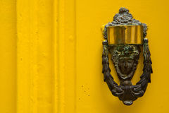 Decorative bronze door handle in the form of a beautiful woman`s. Head on a yellow painted door. Malta Royalty Free Stock Photos