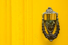 Decorative bronze door handle on a yellow painted door. Malta. Decorative bronze door handle in the form of a beautiful woman`s head on a yellow painted door Stock Images
