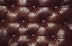 Decorative brown background of genuine leather. Decorative background of genuine leather capitone texture. Texture of genuine leather upholstered furniture Royalty Free Stock Image